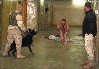 Man bedreigt liggende naakte man met aangelijnde herdershond. Locatie is gang Abu Ghraib
